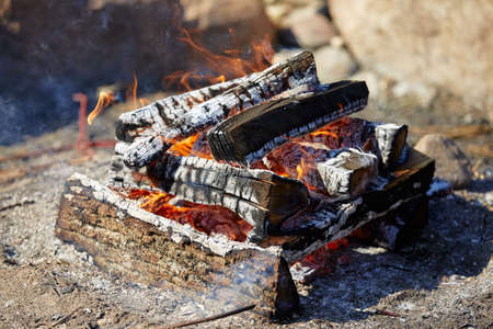 burning firewood and coals with a big flame with smoke, outdoors