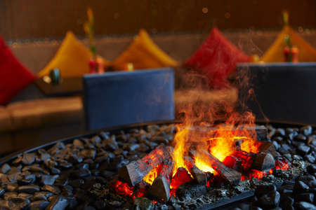 burning firewood and coals with a big flame with smoke