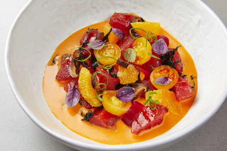 vegetable soup in a white bowl, with cherry tomatoes, peppers, beets and herbs