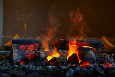firewood and coals lying and burning in a big flame with smoke