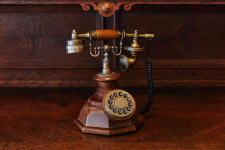 old wired wood-iron telephone, antique, on brown wooden background