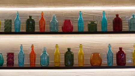 mehrfarbige Flaschen in verschiedenen Formen stehen in einer Reihe in den Regalen Standard-Bild