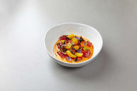 vegetable soup in a white bowl, with cherry tomatoes, peppers, beets and herbs, on a gray background
