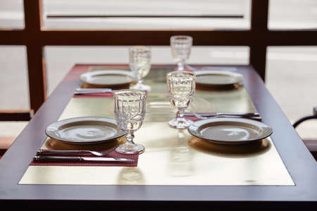 a table on which dishes and cutlery are laid out, table setting, glasses and plates in bright colors