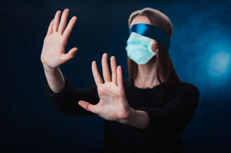 a girl blindfolded, with a blue ribbon, looking for coronavirus medicine Фото со стока