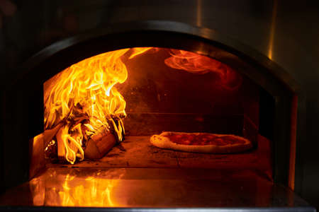 Italian pizza is cooked in a wood-fired oven Stockfoto