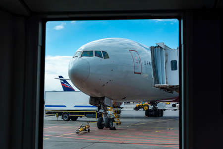 Travel, transportation and airlines concept - a passenger plane is standing at the airport in a parking space awaiting departure, the process of preparing for the flight is in progress