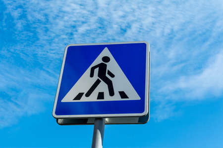 Blue pedestrian crossing sign close up against a cloudy sky 版權商用圖片