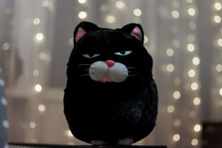 Soft toy cat with an angry expression on his face on the background of blurred garland.