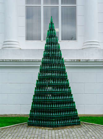 Christmas tree from green glass wine bottles against a white wall, Abrau-Durso.