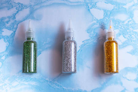 Set of emerald, silver and gold glitters in plastic bottles for soap making on the surface of blue marble, close up, full size, flat lay 版權商用圖片