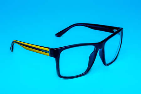 Computer eye protection glasses with a yellow shackle close up on a blue background, isolation