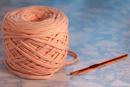 A coil of large knitted yarn of peach color with orange shiny hook on the surface of blue marble 版權商用圖片