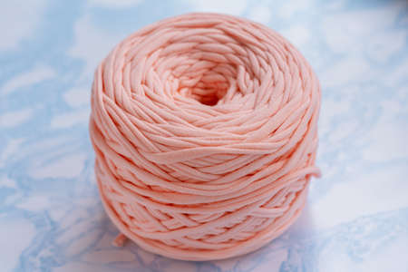A coil of large knitted yarn of peach color on the surface of blue marble 版權商用圖片