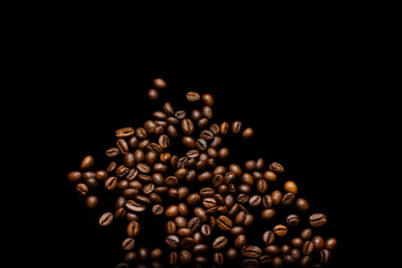 Scattered grains of roasted, fragrant coffee on a black background, isolation, flat-lay, copy space 版權商用圖片