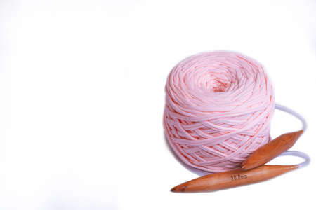 A coil of large knitted yarn of peach color with 20 mm circular bamboo needles on white background, isolation, copy space