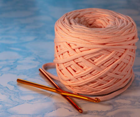 A coil of large knitted yarn of peach color with two orange shiny hooks on the surface of blue marble