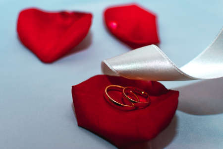 Wedding rings on a red rose petal with a white satin ribbon on the table