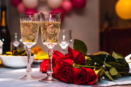 Festive glasses with sparkling champagne on the table of the newlyweds with a bouquet of red roses, selective focus, wedding decoration of the interior