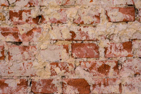 Wall of red crumbling brick, covered with white stucco, background 版權商用圖片