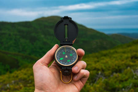 Travel, camping, orienteering and navigation concept - black magnetic compass close-up in a man s hand, blurred landscape background 版權商用圖片