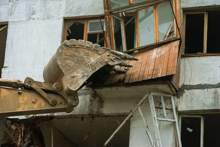 Close-up of an excavator bucket destroys a wooden balcony 版權商用圖片
