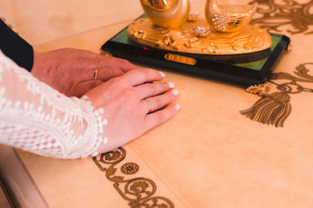 Hands of the newlyweds with wedding rings after the wedding ceremony on a luxurious table 版權商用圖片