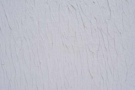 Part of the texture of a white wall decorated with decorative putty