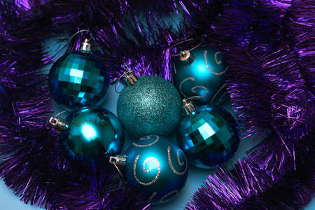 Christmas blue toys lie surrounded by festive purple tinsel, top view