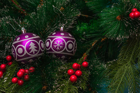 Two purple festive balloons with the image of a Christmas tree and snowflakes hanging on artificial branches of a spruce