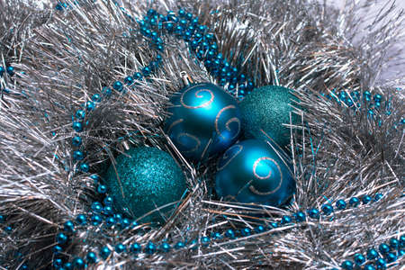 Christmas blue toys lie on a festive silver tinsel, top view 版權商用圖片