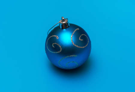 Christmas blue toy with silver spirals for decoration on a turquoise background 版權商用圖片