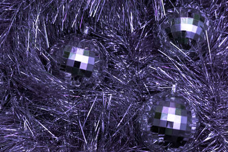 Christmas toys in the form of disco balls lie on a festive silver tinsel, top view, purple color