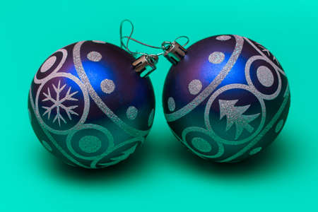 Two big blue festive balloons with the image of a Christmas tree and snowflakes on green background