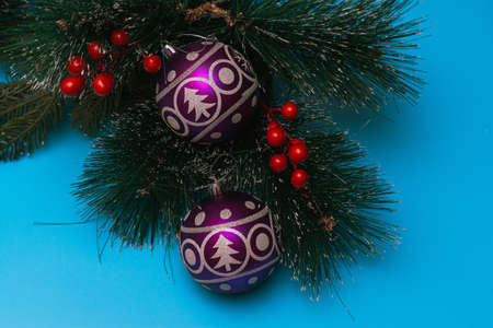Two purple festive balloons with the image of a Christmas tree and snowflakes lie on artificial branches of a spruce, blue background, flatlay