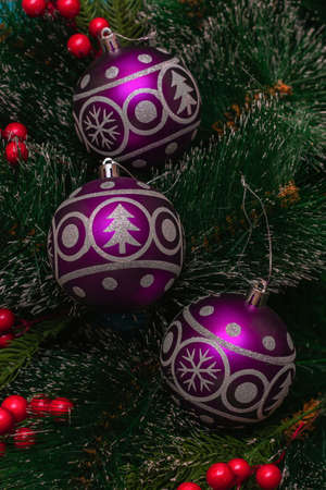 Three purple festive balloons with the image of a Christmas tree and snowflakes hanging on artificial branches of a spruce