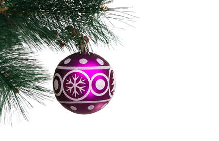 Christmas festive purple balloon with the image of a spruce and snowflakes for decoration hanging on artificial branches of a fir-tree on a white background, isolated, soft focus