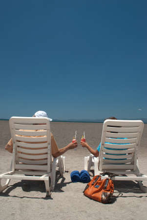 Couple having a refreshment drink at the beach. photo