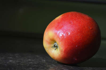 red-yellow apple lies on the table