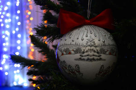 Beautiful, festive, Christmas, New Year's ball on a green spruce. flickering garlands in the background