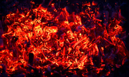 abstraction yellow-red coals smolder against the background of the night, the remains of firewood
