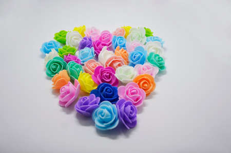 heart of multi-colored artificial roses on a white background. heart is a symbol of declaration of love and fidelity