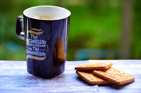 cup of aromatic coffee and cookies on a background of green foliage. motivational inscription in Russian on the cup