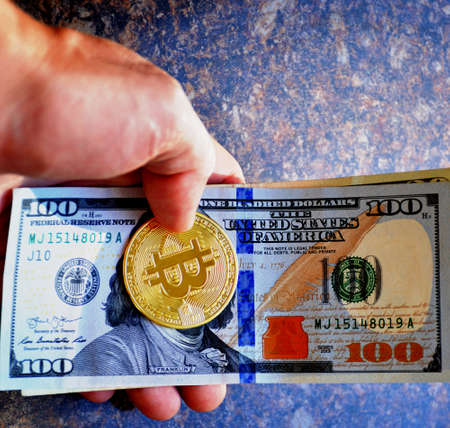 male hand holding gold bitcoin coin and paper dollar bills 写真素材