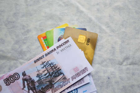 on a light fabric background are bank cards covered on top with a bundle of Russian bills of different denominations