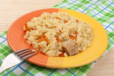 pilaf with carrots in a yellow-orange plate photo