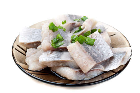 pieces of herring on a plate isolated on a white background