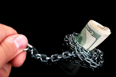 pulls money from the chain on a black background Stock Photo