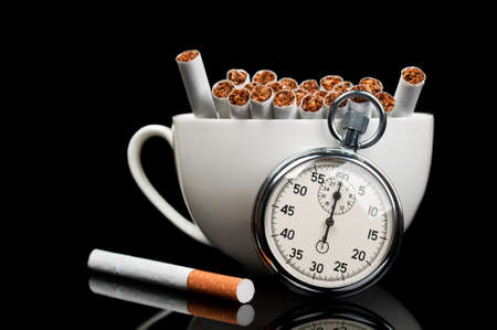 cup full of cigarettes and stopwatch isolated on a black background photo