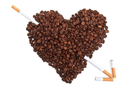 Roasted coffee beans in the shape of the heart with cigarettes isolated on a white background photo